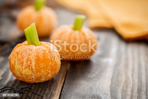 Healthy Halloween snacks for kids.  Tangerine jack o'lanterns made of tangerines and celery stick with spider decoration.  These healthy halloween are fun food for kids on rustic wood table.