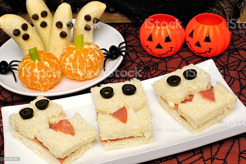 Healthy Halloween monster sandwiches, banana ghosts and orange pumpkins stock photo