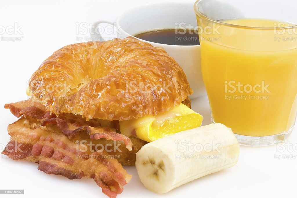 Healthy ham, bacon and cheese breakfast croissant with fruit bildbanksfoto