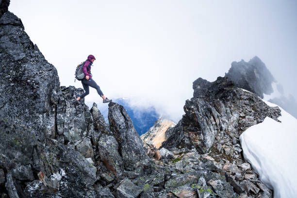 Healthy happy woman hiking on a mountain ridge stock photo
