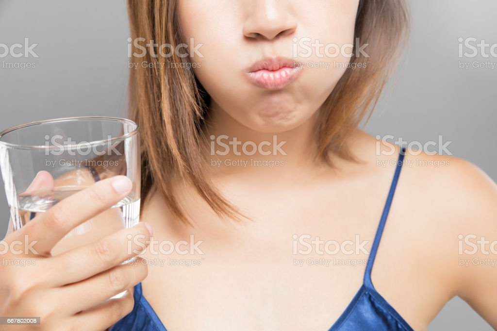 Healthy happy woman rinsing and gargling while using mouthwash from a glass, During daily oral hygiene routine, Portrait with bare shoulders, Dental Health Concepts stock photo