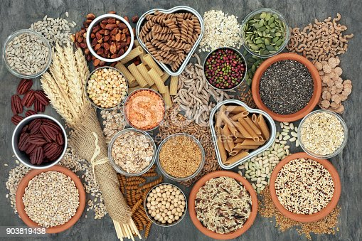 Healthy high fibre dietary food concept with whole wheat pasta, legumes, nuts, seeds, cereals, grains and wheat sheaths. High in omega 3, antioxidants, vitamins. On marble background top view.