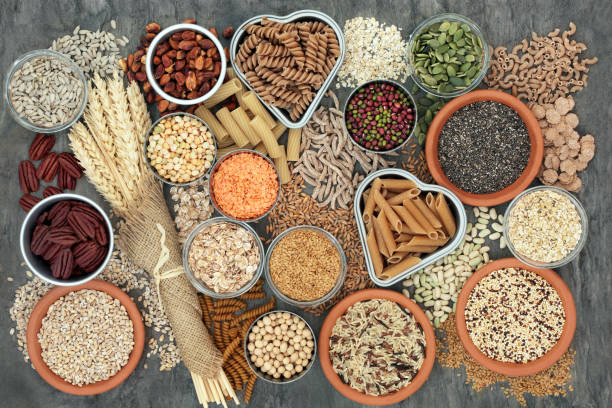Healthy High Fibre Food Healthy high fibre dietary food concept with whole wheat pasta, legumes, nuts, seeds, cereals, grains and wheat sheaths. High in omega 3, antioxidants, vitamins. On marble background top view. fiber stock pictures, royalty-free photos & images