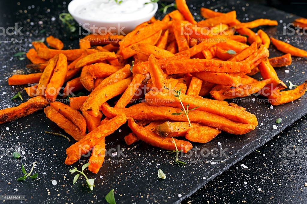 Healthy Homemade Baked Orange Sweet Potato Fries with fresh cream - fotografia de stock