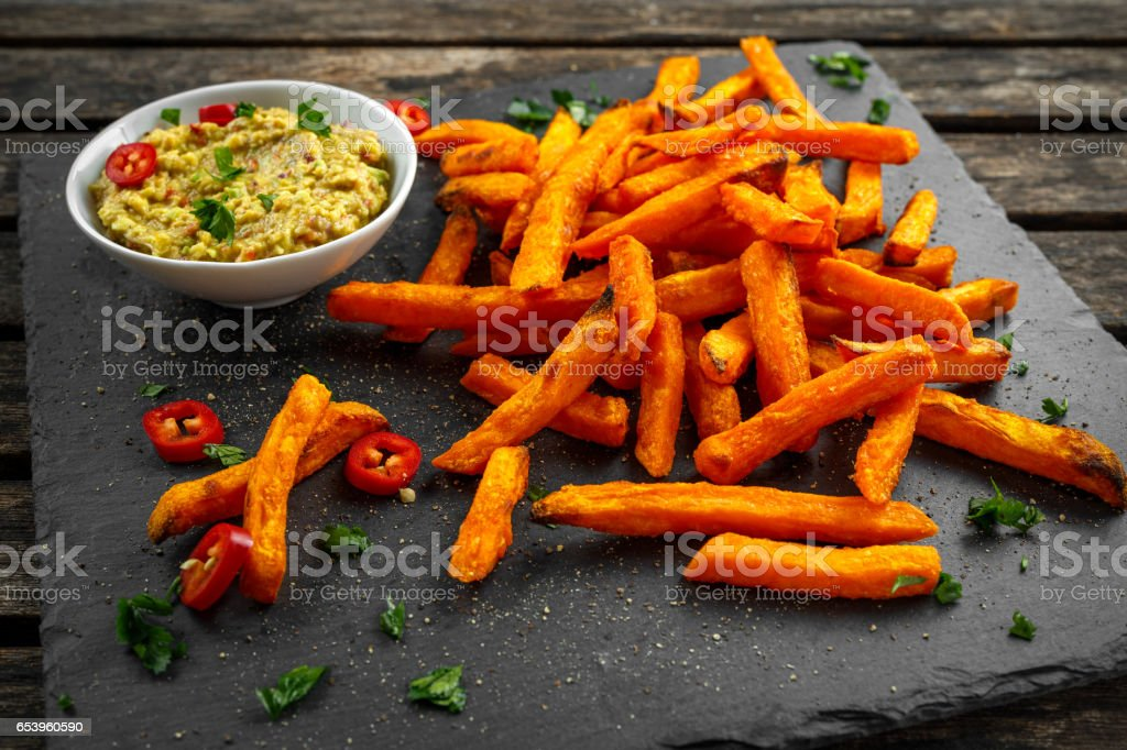 Healthy Homemade Baked Orange Sweet Potato Fries with guacamole, salt, pepper on stine, stone board stock photo