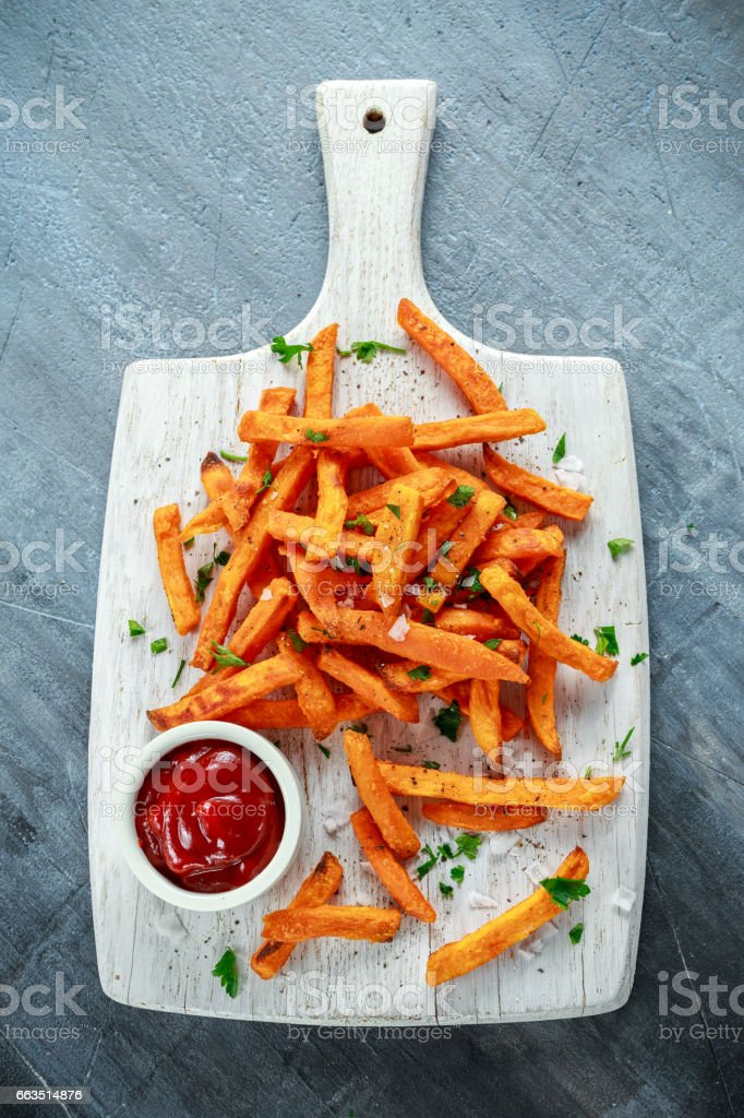 Healthy Homemade Baked Orange Sweet Potato Fries with ketchup, salt, pepper on white wooden board stock photo