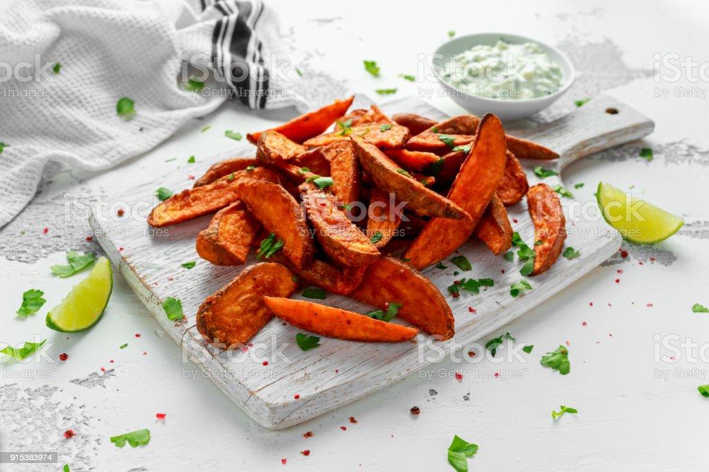 Healthy Homemade Baked Orange Sweet Potato wedges with fresh cream dip sauce, herbs, salt and pepper stock photo