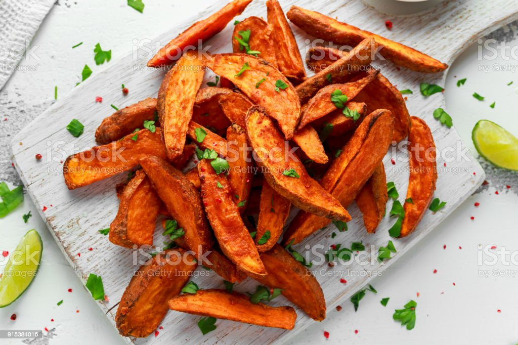 Healthy Homemade Baked Orange Sweet Potato wedges with fresh cream dip sauce, herbs, salt and pepper - fotografia de stock