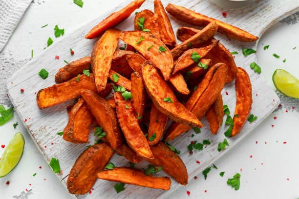 Healthy Homemade Baked Orange Sweet Potato wedges with fresh cream dip sauce, herbs, salt and pepper Healthy Homemade Baked Orange Sweet Potato wedges with fresh cream dip sauce, herbs, salt and pepper sweet potato stock pictures, royalty-free photos & images