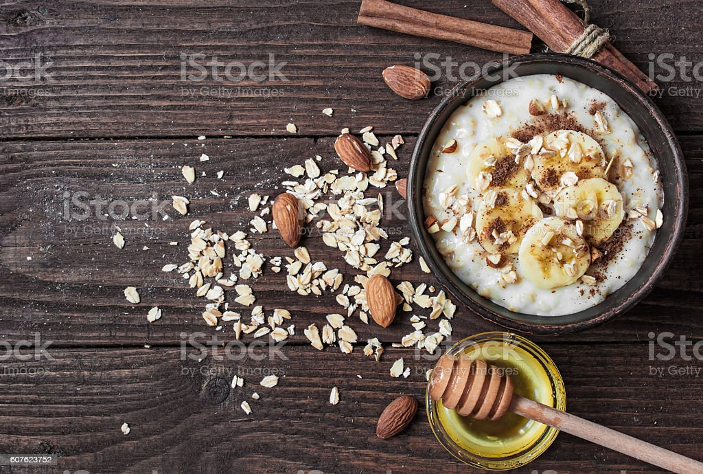 healthy homemade oatmeal porridge with nuts, banana, cinnamon and honey stock photo