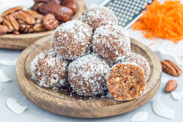Healthy homemade paleo energy balls with carrot, nuts, dates and coconut flakes, on wooden plate, horizontal stock photo