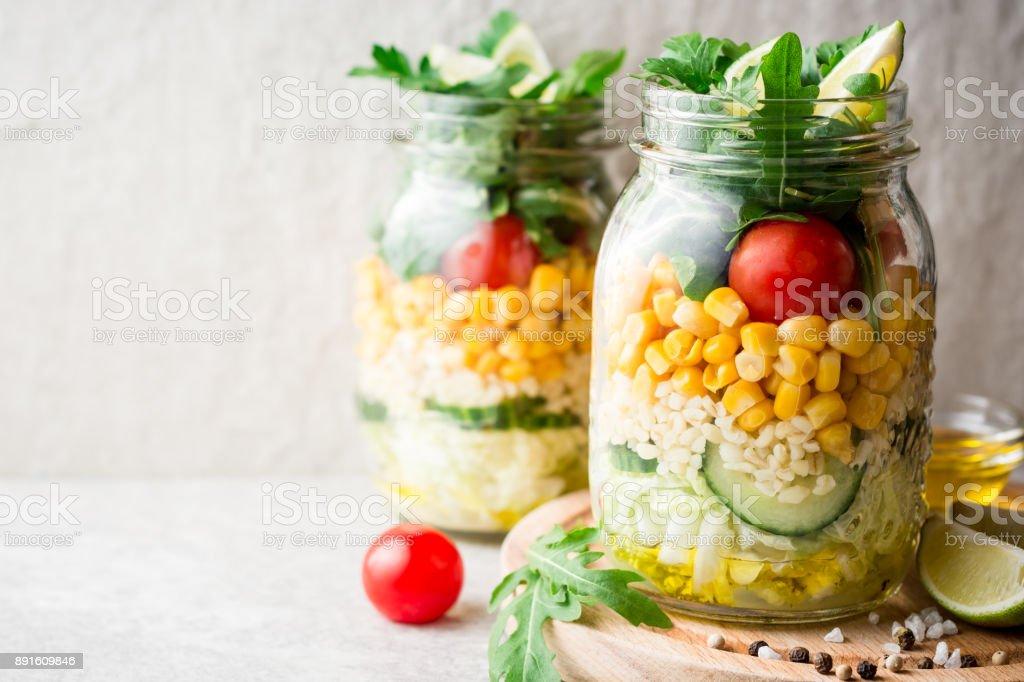 Salades de maison saines avec boulgour, légumes et citron vert en bocaux mason sur fond gris de pierre. - Photo