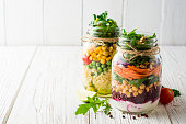 ひよこ豆、ブルガーと白い木製の背景に石工の jar ファイルの野菜とヘルシーな自家製サラダ。