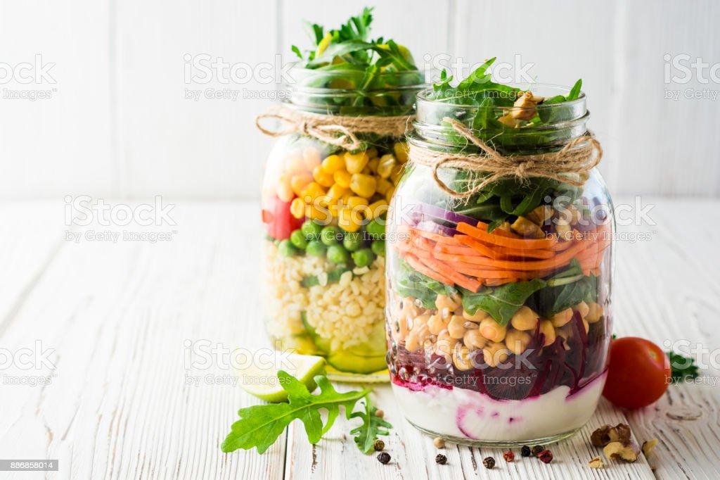 Salades maison saines avec pois chiches, le boulgour et légumes dans des bocaux mason sur fond en bois blanc. - Photo