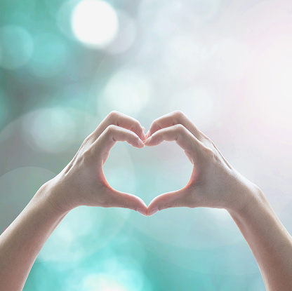 istock Healthy human hand in heart shape showing love friendship on blurred abstract cool blue green sky color bokeh background: Global eco environment CSR natural resource awareness/ concept/ campaign/ idea 964261494