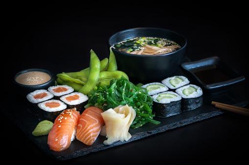 istock Healthy japanese bento lunch with salmon maki, cucumber maki, nigiri salmon sushi, seaweed salad, edamame and miso soup tofu on black background. 1190771437