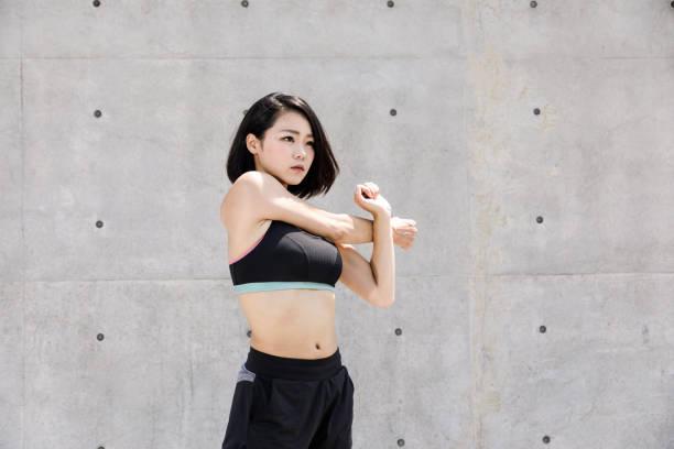 健康な日本女性は屋外ストレッチします。 ストックフォト