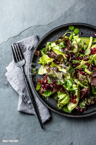 Healthy lettuce salad with watercress salad and pomegranate on black plate. Gray slate background