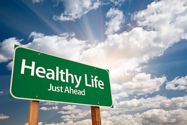 Healthy Life Green Road Sign Over Clouds stock photo