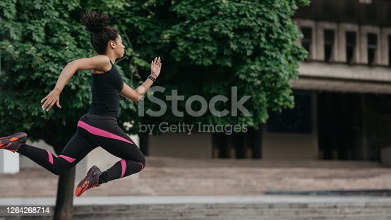 Healthy lifestyle and energy in body. Athlete african american girl in sportswear froze in air in jump, running at city at summer, profile, panorama, copy space