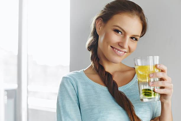 gesunder lebensstil und speisen. frau trinkt wasser und früchte). entgiften. - wasser trinken abnehmen stock-fotos und bilder