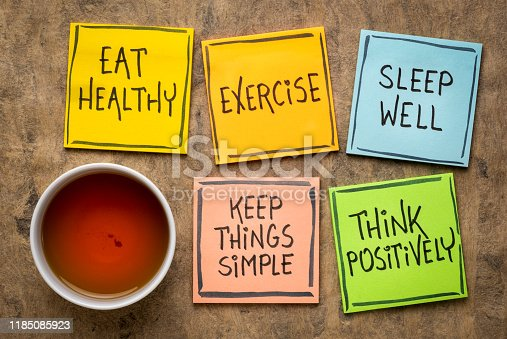 healthy lifestyle and wellbeing concept - a set of inspirational reminder notes with a cup of tea: eat healthy, exercise, seep well, keep things simple, think positively