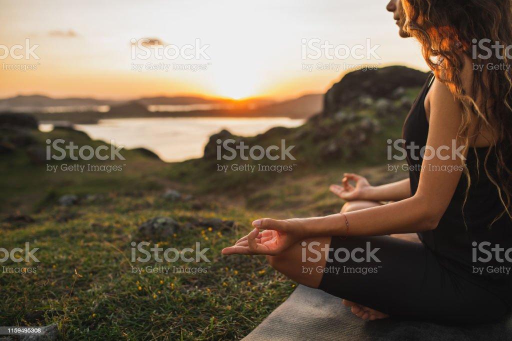 Gezonde lifestyle en yoga concept. Close-up handen. Woman do yoga buitenshuis bij zonsopgang in Lotus positie. Vrouw oefenen en mediteren in de ochtend. Natuur achtergrond. - Royalty-free Alleen volwassenen Stockfoto