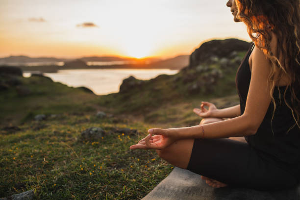 Healthy Lifestyle and Yoga Concept. Close-up hands. Woman do yoga outdoors at sunrise in lotus position. Woman exercising and meditating in morning. Nature background. Healthy Lifestyle and Yoga Concept. Close-up hands. Woman do yoga outdoors at sunrise in lotus position. Woman exercising and meditating in morning. Nature background. wellbeing stock pictures, royalty-free photos & images
