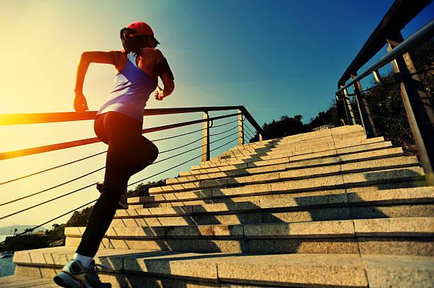 Estilo de vida saludable asiática mujer corriendo por las escaleras en la playa - foto de stock