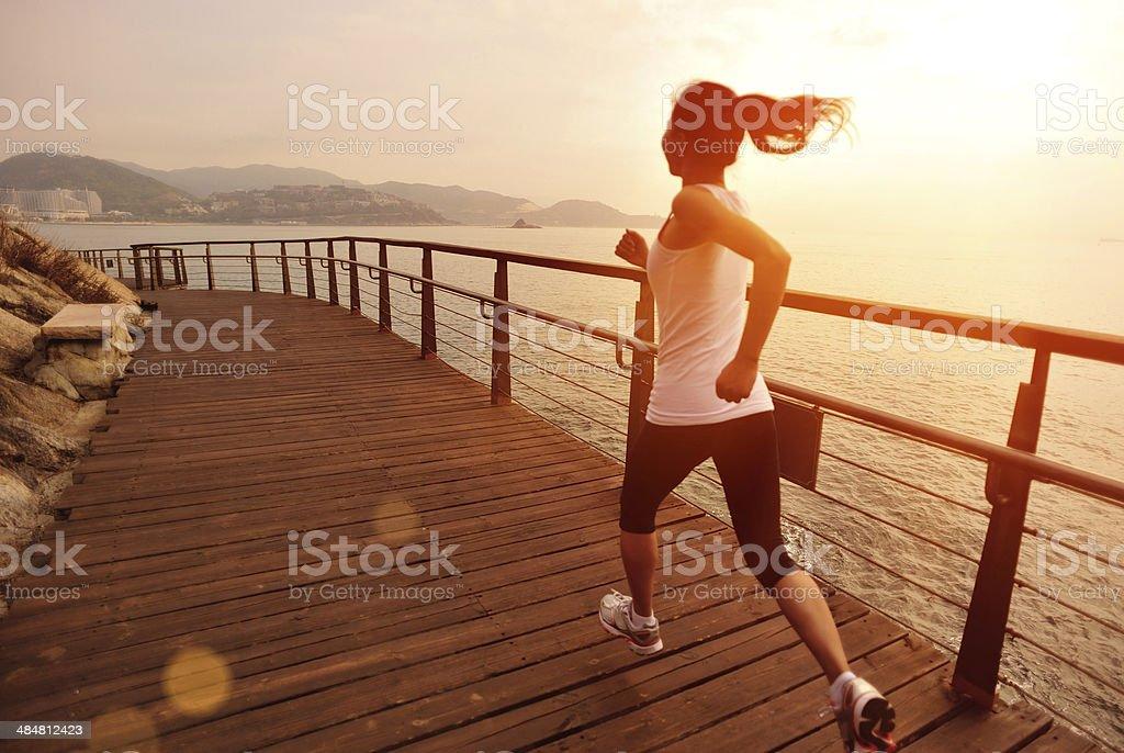 Estilo de vida saludable mujer asiática corriendo en pista de madera junto al mar foto de stock libre de derechos