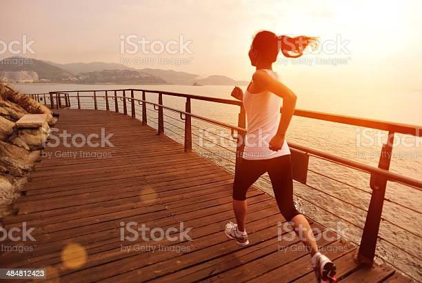 Estilo De Vida Saludable Mujer Asiática Corriendo En Pista De Madera Junto Al Mar Foto de stock y más banco de imágenes de Actividad
