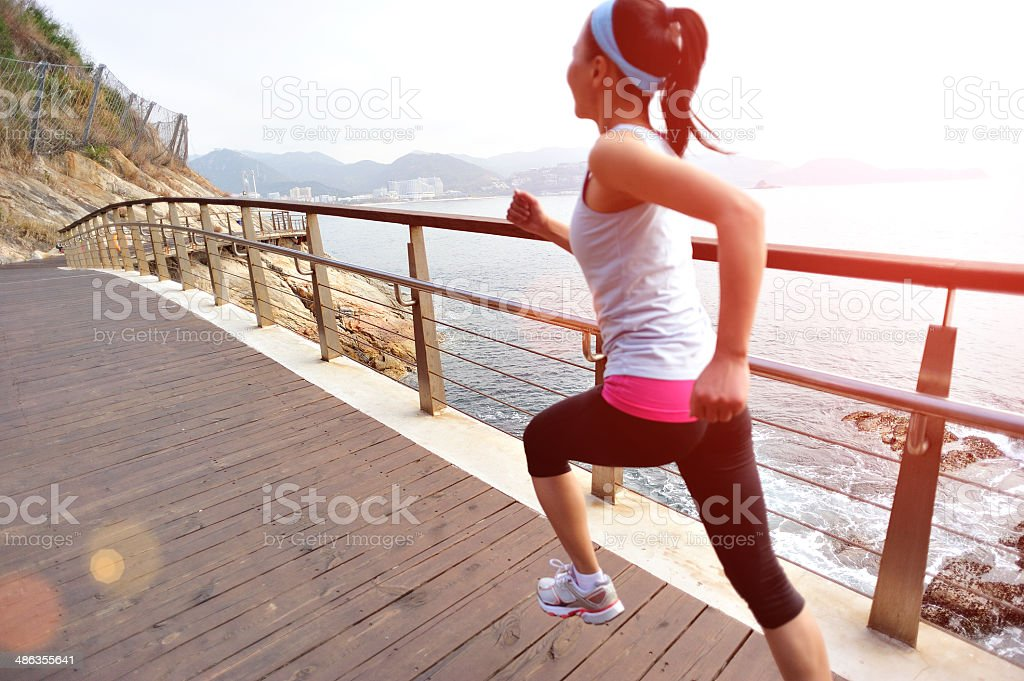 healthy lifestyle asian woman running at wooden trail seaside royalty-free stock photo