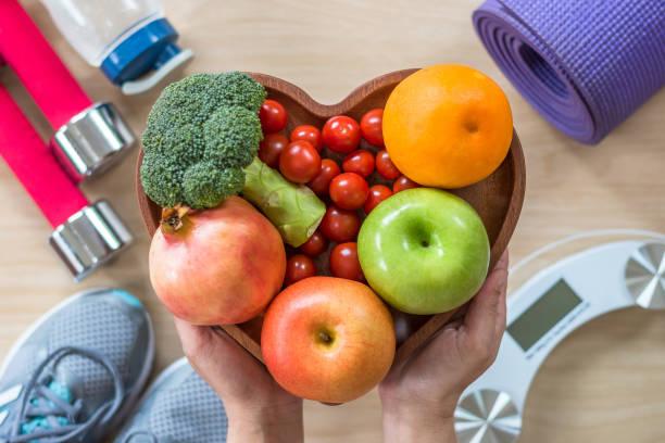 健康的生活方式概念, 乾淨的食物好健康膳食在心臟盤與運動健身房健美操健身訓練班設備、體重秤和運動鞋 - 健康飲食 個照片及圖片檔