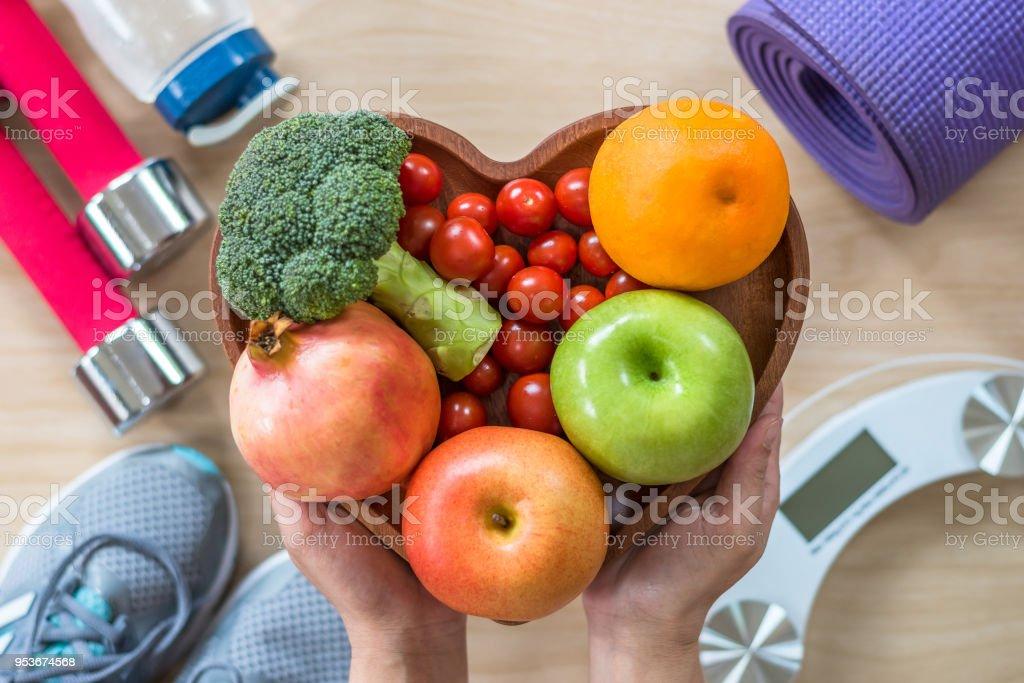 Concepto de estilo de vida saludable, comida limpia buena salud dietética en plato de corazón con equipo de gimnasio deportivo cuerpo aeróbico ejercicio entrenamiento entrenamiento clase, zapatos de deportes y escala de peso en gimnasio - foto de stock