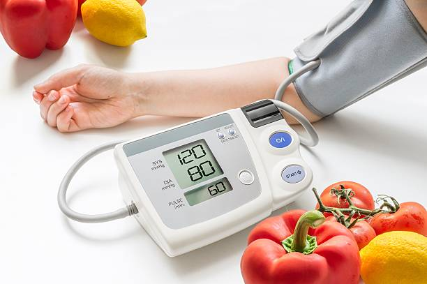 Healthy lifestyle concept. Woman is measuring blood pressure with monitor. stock photo