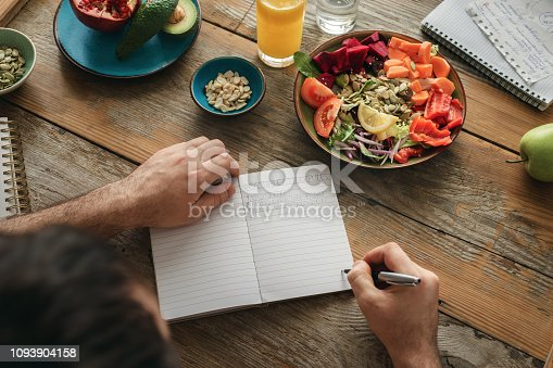 Man makes a list of healthy food. Healthy lifestyle diet food concept
