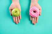 Healthy lifestyle, food and sport concept. Top view of healthy versus unhealthy. Woman hand holding donut and green apple on blue pastel background.