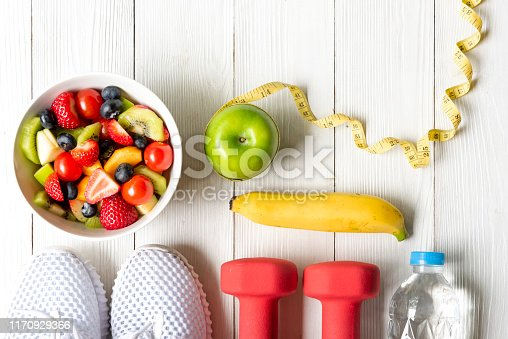Healthy lifestyle for women diet with dumbbells sport equipment, sneakers, measuring tape, fruit healthy green apples and bottle of water on wooden.  Healthy Concept.