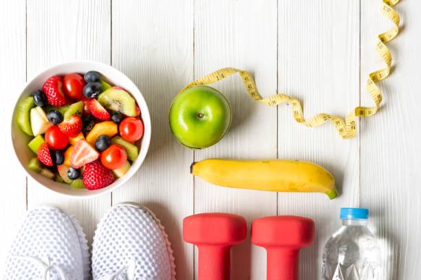 健康的生活方式為婦女的飲食與啞鈴運動設備,運動鞋,測量磁帶,水果健康的綠色蘋果和木瓶水。 健康理念。 - 健康的生活方式 個照片及圖片檔