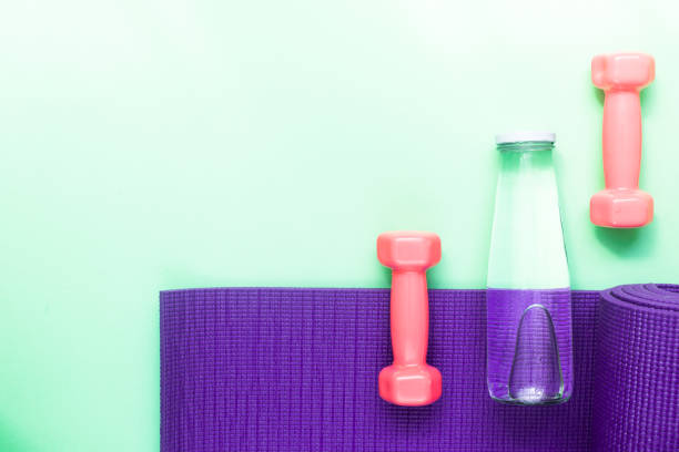 Healthy lifestyle frame concept with fat burning fruits, detox water, gym mat and hand weights stock photo