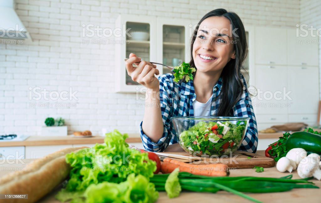 Healthy lifestyle. Good life. Organic food. Vegetables. Close up portrait of happy cute beautiful young woman while she try tasty vegan salad in the kitchen at home. - Foto stock royalty-free di Abbigliamento casual