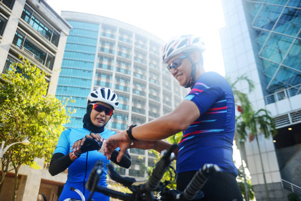 Healthy lifestyle Malaysian cyclists making preparation before cycling Asian Muslim lady cyclist in hijab and a man cyclist female biker resting stock pictures, royalty-free photos & images