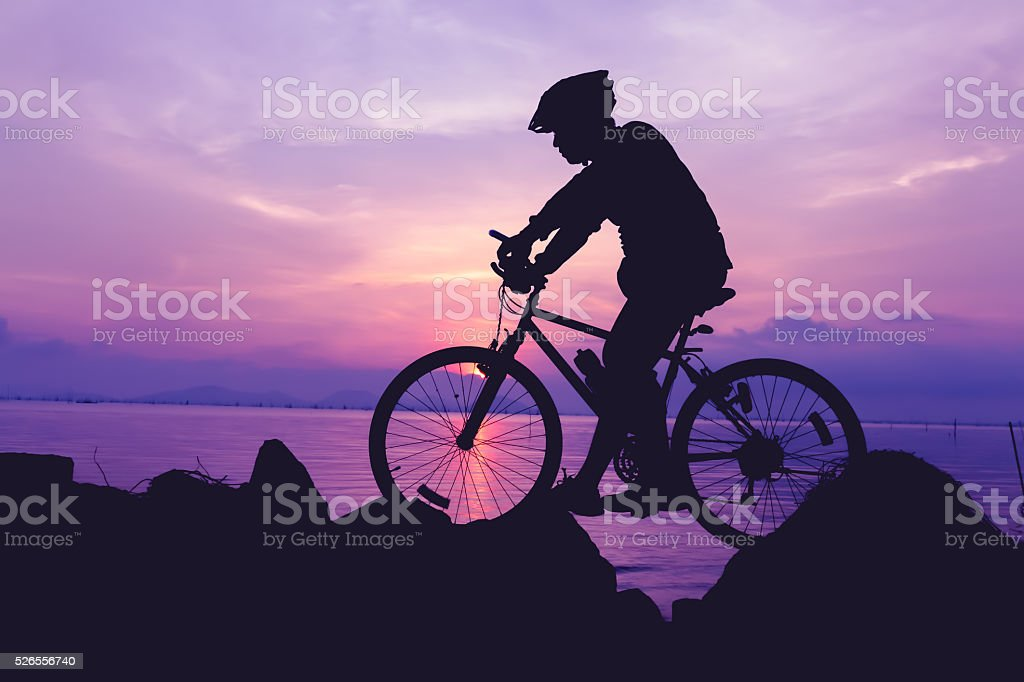 Healthy lifestyle. Silhouette of bicyclist riding the bike at se stock photo