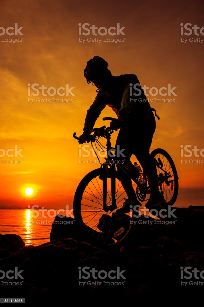 Healthy lifestyle. Silhouette of bicyclist riding the bike at seaside. Outdoors. royalty-free stock photo