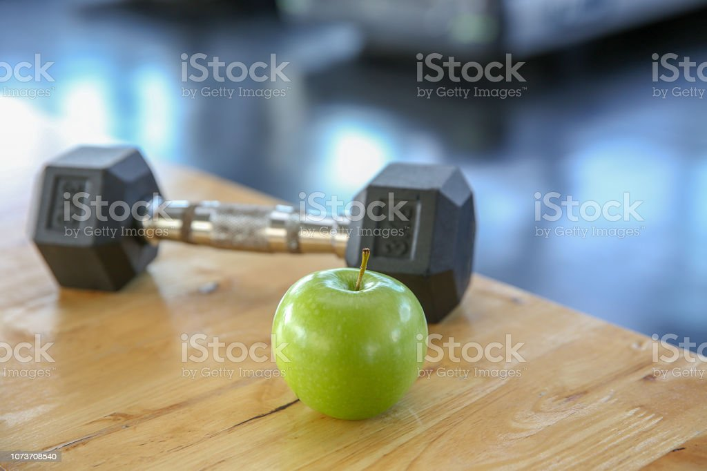 Healthy lifestyle sport. Dumbbells, and healthy food on wooden. green...