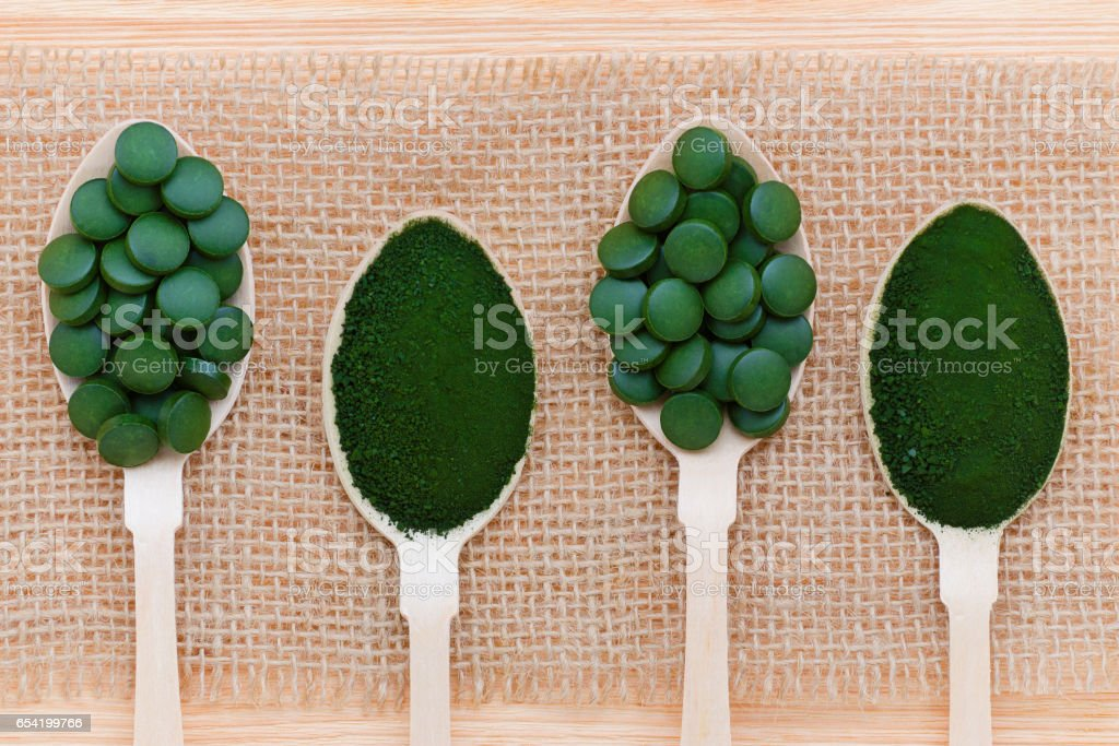 healthy lifestyle, superfood, seaweed, spirulina and chlorella pills and powder in wooden spoons stock photo