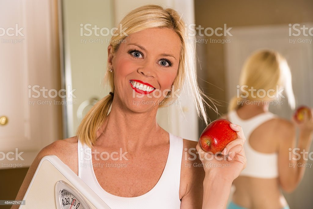 Healthy Lifestyle:  Weight conscious woman holding scale.  Reflection in mirror. royalty-free stock photo