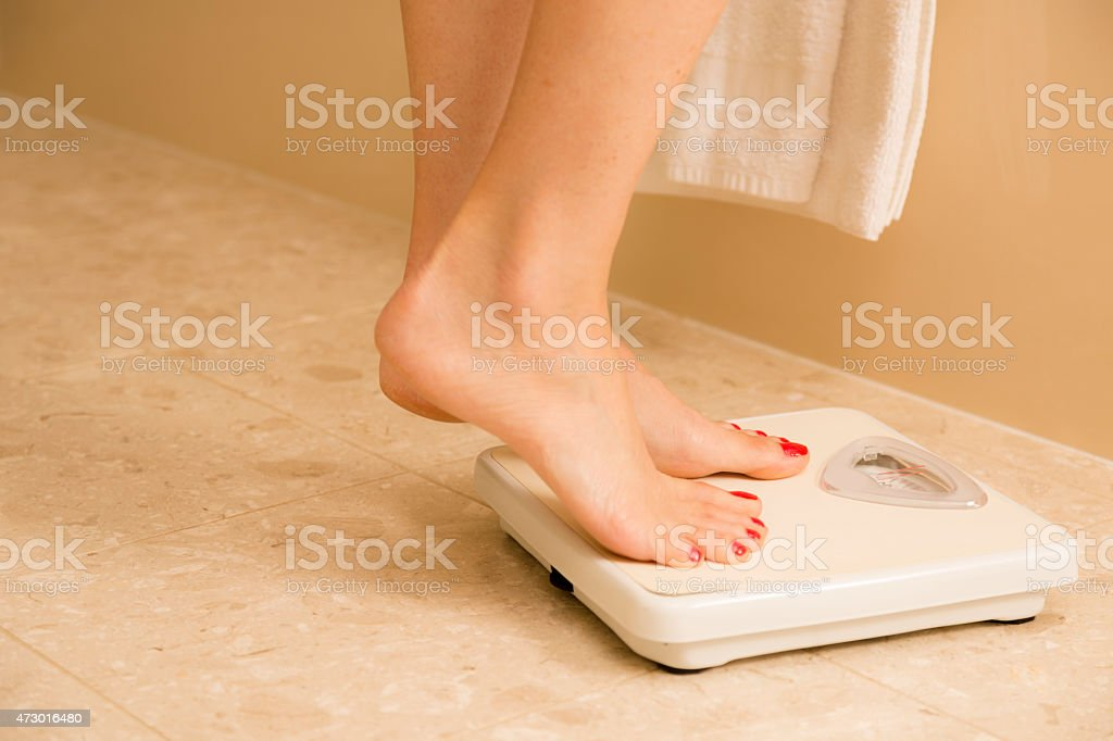 Healthy Lifestyle:  Weight conscious woman standing on bathroom scale. Dieting. stock photo