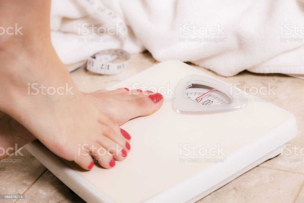 Healthy Lifestyle:  Weight conscious woman steps on bathroom scale. stock photo