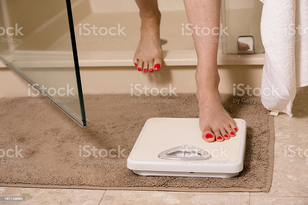 Weight Loss. Woman stepping out of shower. Scale.